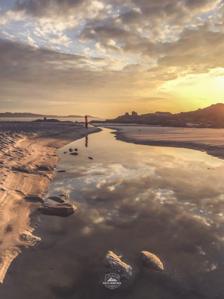 Colores cálidos del atardecer sobre las aguas de un río que fluye hacia la playa